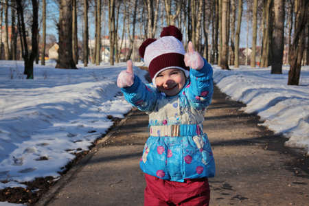 Little girl showing thumbs up standing against winter snowy park in sunny day 免版税图像
