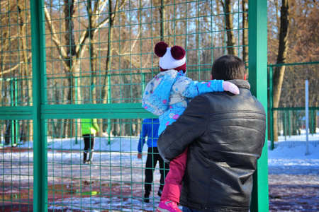Father with child in the field. View from back, March 3, 2016, Tula, Russia