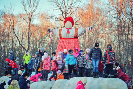 Traditional Maslenitsa Scarecrow on seeing Russian winter on last day of Shrovetide. Viewers awaiting initiation of ignition. Group of children standing at scarecrows, March 3, 2016, Tula, Russia