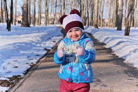Little girl clenched her fists in mittens standing against winter snowy park in sunny day