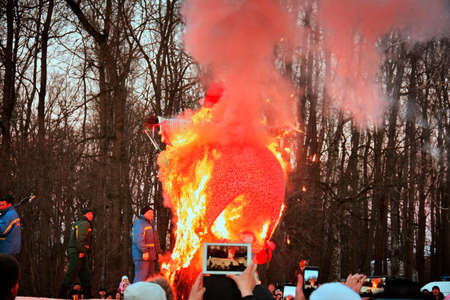 Traditional burning of Maslenitsa Scarecrow on seeing Russian winter on last day of Shrovetide. Audience shoot fire on smartphones and cameras, March 3, 2016, Tula, Russia 新闻类图片