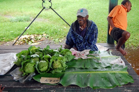 Nuova Guinea: Man saling cavolo sul mercato al villaggio in Papua Nuova Guinea