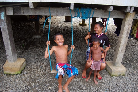 Kids are playing under their house, Mareguina, Papua New Guinea