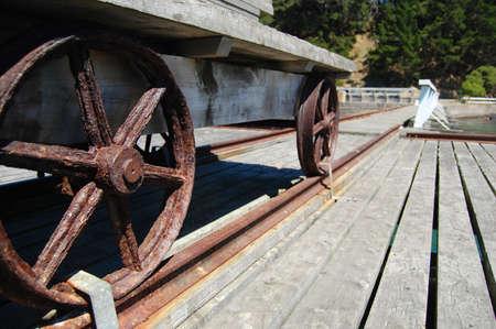 Metal wheels of old wagon on pier, Banks Peninsula, New Zealand Stock Photo - 16304249
