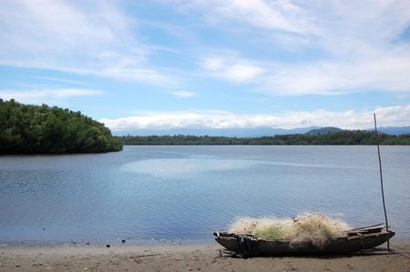 Nuova Guinea: Canoa con rete da pesca sulla costa del fiume, Papua Nuova Guinea