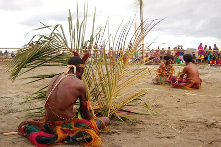 Nuova Guinea: La gente si siede sulla sabbia, festa maschera, Papua Nuova Guinea Editoriali