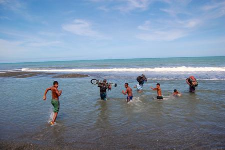 Nuova Guinea: Le persone attraversano il fiume in mare, Papua Nuova Guinea Editoriali