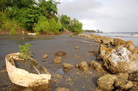 Nuova Guinea: Barca abbandonata con la bassa marea oceano costa rocciosa, entroterra di Papua Nuova Guinea