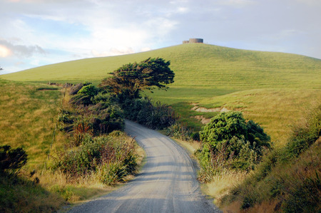 Gravel road turn left at rural area near water tank on hill top, Dargaville, New Zealand photo