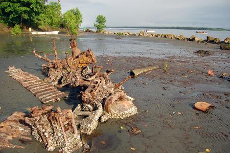 new guinea: Parti di metallo arrugginito abbandonato in barca con la bassa marea costa dell'oceano, Papua Nuova Guinea