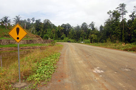 rural area: Yellow warning road sign at gravel road rural area, Indonesia