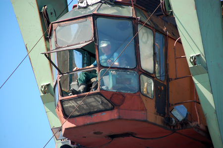 crane bucket: Dockside cargo crane operator at river port Kolyma, Yakutia, Russia