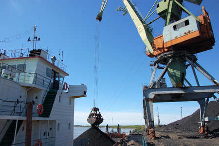 dockside: Dockside cargo crane loads coal at river port Kolyma, Yakutia, Russia Stock Photo