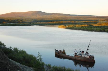 man made object: Abandoned sinked ship at Kolyma river,Yakutia region, Russia Stock Photo