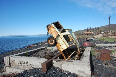 substructure: Old broken rusty abandoned car upside down at sea coast, Pevek town, Chukotka, Russia