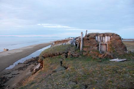 Abandoned broken mud hut at arctic island summer calm sea coast, Chenkul Island, Chukotka, Russia Stock Photo