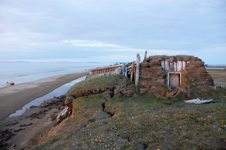 Abandoned broken mud hut at arctic island summer calm sea coast, Chenkul Island, Chukotka, Russia Standard-Bild