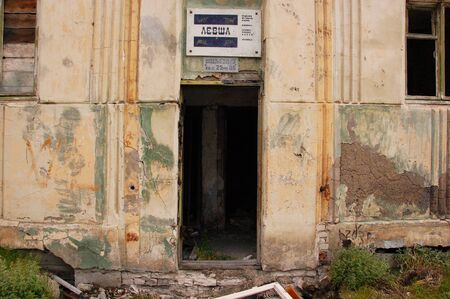 Old information sign above abandoned building entrance, Pevek town, Chukotka, Russia