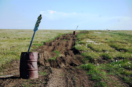road mark: Old oil drum with road mark stake at tundra, Ayon Island, Chukotka, Russia Stock Photo
