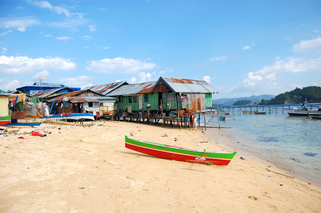 Boats at sand beach village coast with pier, Indonesia