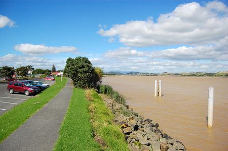 Cars near pedestrian walkway at muddy river coast, Dargaville, Northland, New Zealand