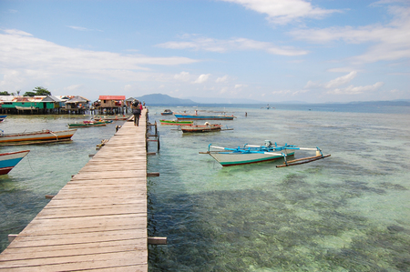 Boats near long village timber pier, Indonesia Stock Photo