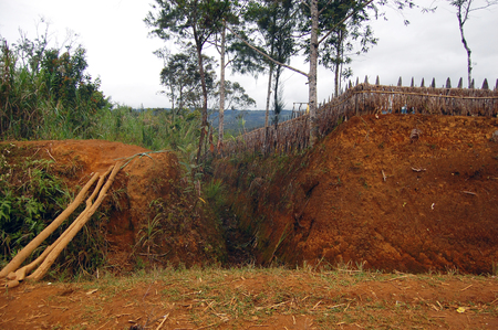 Village ditch with timber fence at rural area, Papua New Guinea