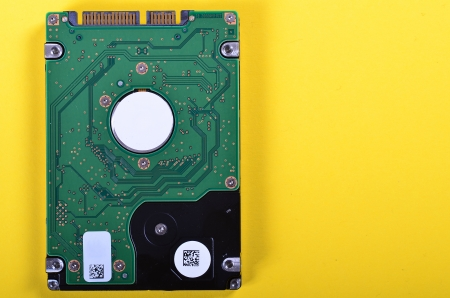 A close up of a sata hard drive isolated on yellow background photo
