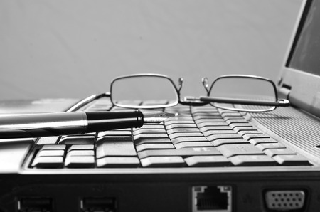 Close up of reading glasses and pen on a laptop photo