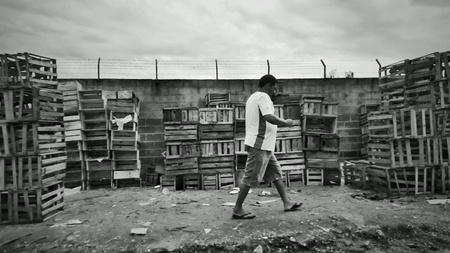 man: Man walks among boxes after fruit fair in Votorantim, SP, Brazil.