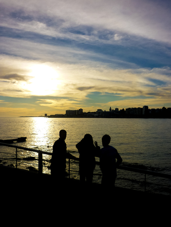 A bunch of teens watching the sunset in the coast in the capital of Uruguay. photo