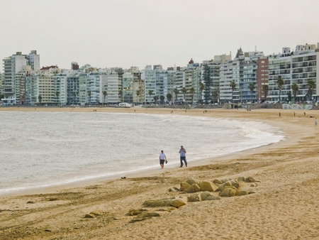 A mature couple walking in the sand of one of the beaches of Montevideo, the capital city of Uruguay in South America Imagens
