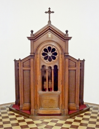 Beautiful isolated confessional made with wood in brown tones