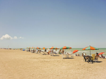 People enjoying a nice day in summer at the beach with the same color pattern of umbrellas in a perspective view in a beach of Argentina, South America. Zdjęcie Seryjne