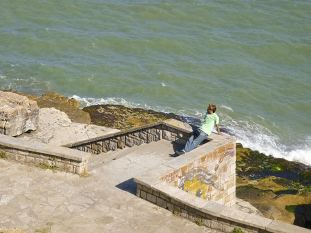 reflexive: Lonely man resting and watching the ocean in the boardwalk of the atlantic coast of Argentina in South America.