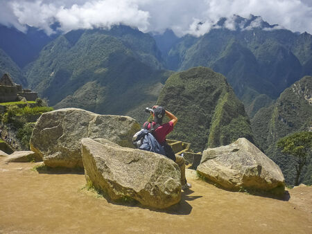 highs: Young man taking photos on the highs in the famous Machu Picchu ancient city of the incas in Peru, South America