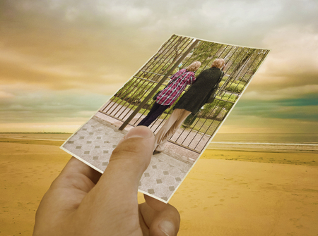 Concept creative collage with a hand holding a photo of a couple of mature women and a nice isolated beach in the background photo