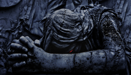 Digital edited and manipulated close up photo of a marble statue of an angel praying with evil eyes expression