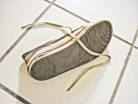 Worn sneaker on the floor with untied shoelaces photo