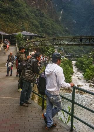 Native and tourist watching the flow of urubamba river in aguas calientes town, the exotic village in which people taking the bus to go to the ancient city of incas Machu Pichu in Peru