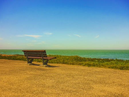 far away look: Beauty and tranquil landscape scene at day with a wood chair toward the sea with nobody at the boardwalk of Punta del Este, the most famous seaside resort of Uruguay Stock Photo
