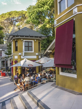 luxuries: CARILÓ BUENOS AIRES, ARGENTINA, JANUARY 2014 - Group of people eating and drinking in a beautiful and original commercial zone surrounded by nature in one of the most luxuries seaside resorts of Argentina.