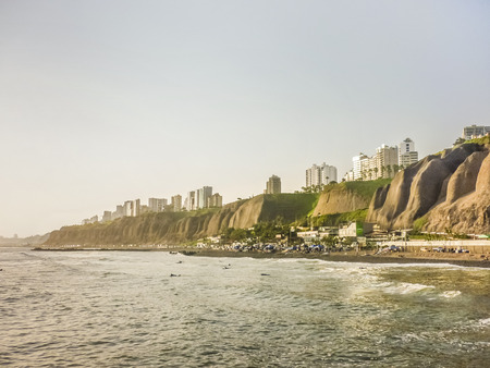 People swimming in the pacific ocean coast of Lima with whis modern buildings and his tall ravines. Imagens