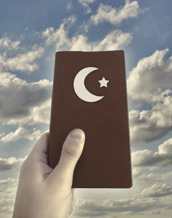 Religious islamic concept photo collage showing a hand holding a islamic book against cloudy sky background.