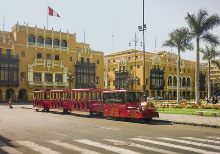 municipal editorial: Plaza Mayor in the historic center of Lima city in Peru South America with a beautiful colonial style yellow buildings and a tourist little red train as the main subjects.