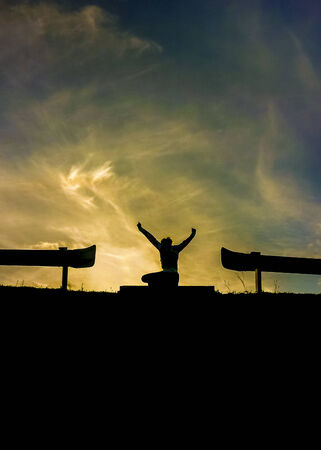 highs: Success or happiness conceptual photo back view of a young woman silhouette in highs with his arms up Stock Photo