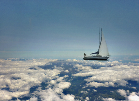navigating: Dreamy fantasy photo collage of a man navigating with a sailboat through the clouds with a clean blue sky at the background.