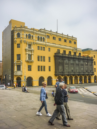municipal editorial: LIMA, PERU, APRIL 2014 - People walking at the street with a beautiful colonial style yellow building at background in the historic center in Plaza Mayor of Lima city in Peru, South America