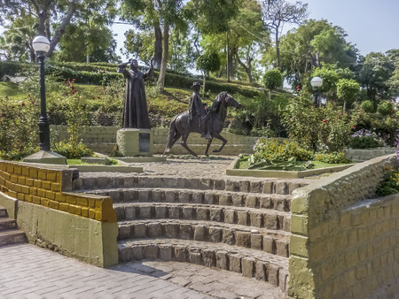 distric: Woman and man riding a horse sulpture in the nice and elegant urban distric called barranco located in the city of Lima in Peru.