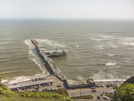 highs: Aerial view of the city of Lima at daytime with the pacific ocean as the main subject.